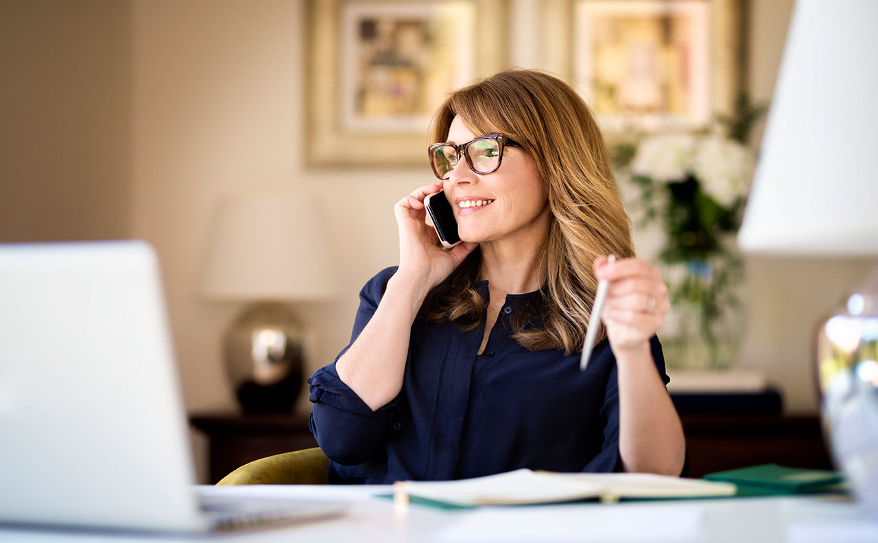 woman working from home on computer, talking on phone